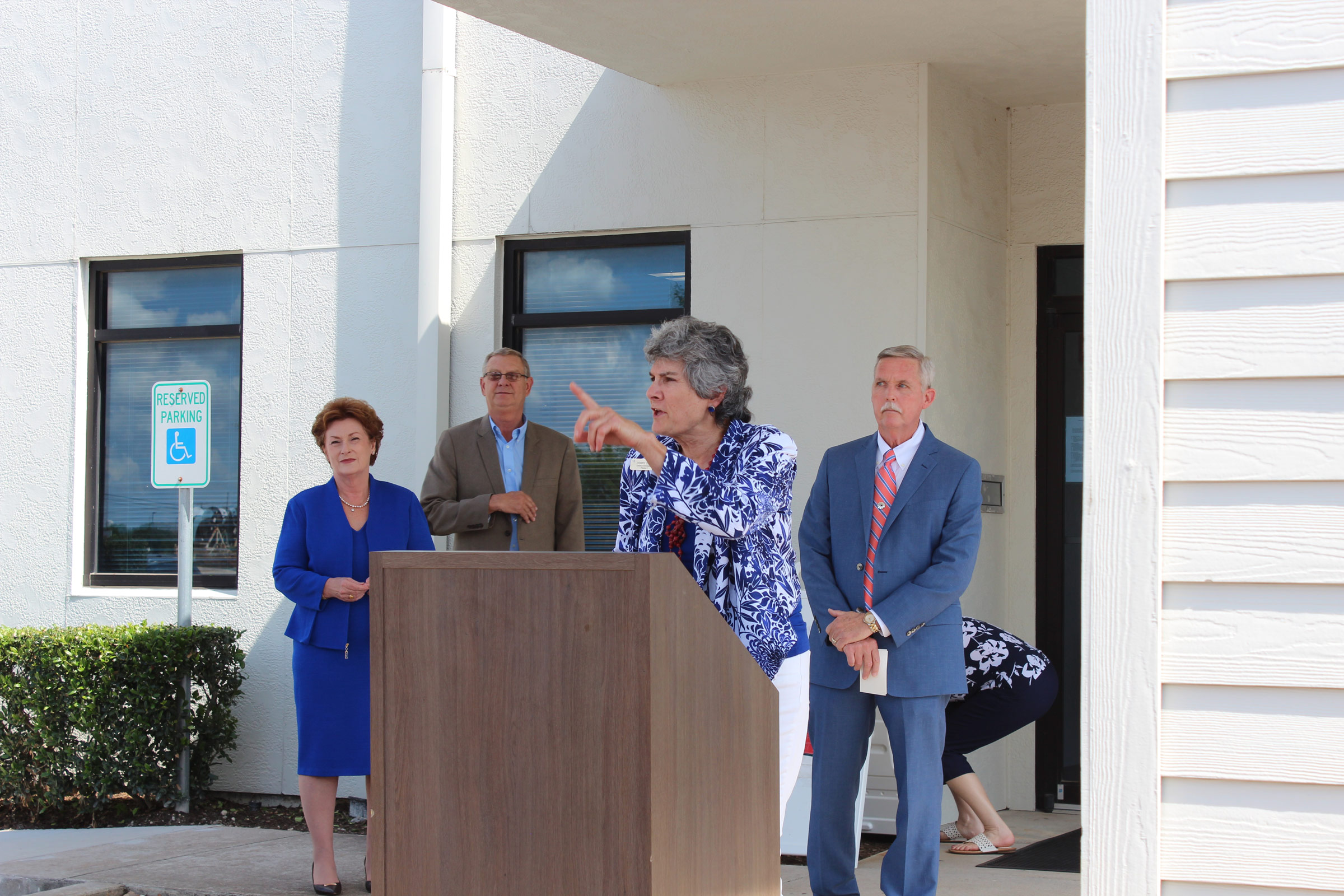 Commissioner Cook speaks at the outdoors ribbon cutting ceremony for the WCCHD. Marlene McMichael, Board Chair, John Teel, Exec. Director, and Precinct 4 Commissioner Larry Madsen are in the background.