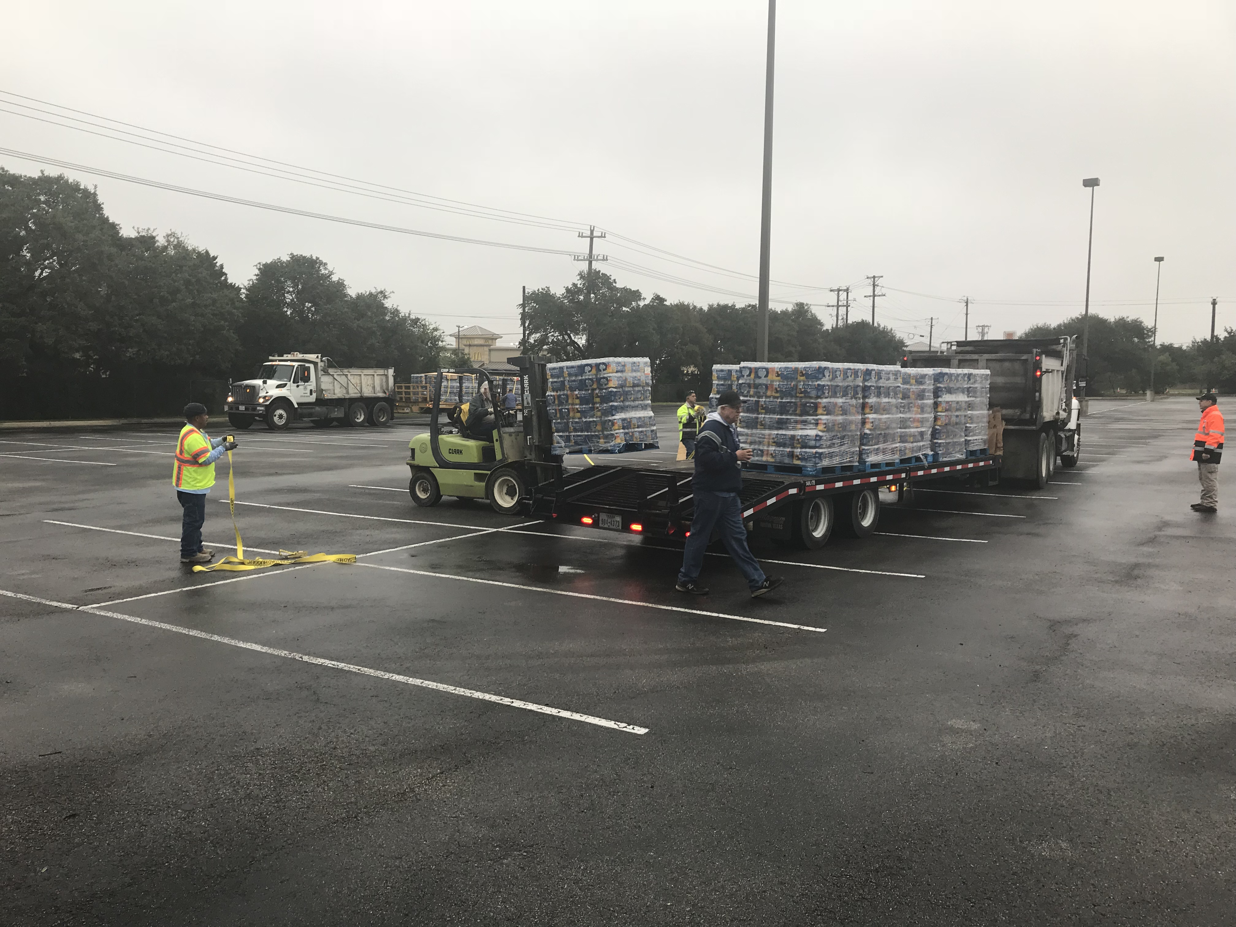 Cases of water are being unloaded from a flatbed truck at the Kelly Reeves Athletic Complex distribution center.