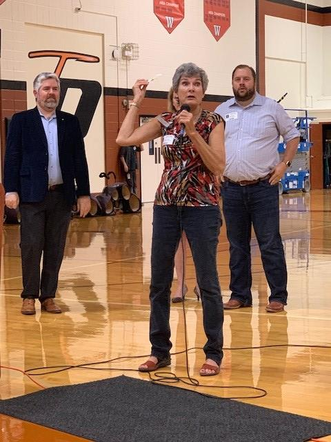 Commissioner Cook stands with a mic in hand speaking at the Westwood High School gym encouraging students to register to vote. Behind her are left Austin Council Member Jimmy Flannigan and right State Representative John Bucy.